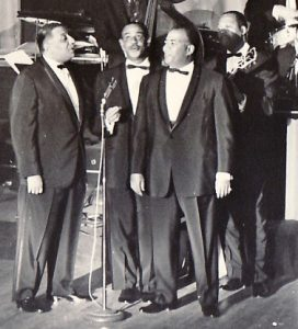 Four brothers in suits and bowties standing and singing into a mic.