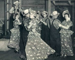 Black and white image of people dancing in what looks like a barn in floral dresses and overalls with plaid shirts.