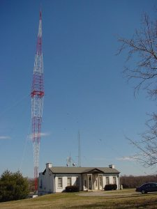 Color photograph of a red and white transmitter near a white house on a blue sky day.