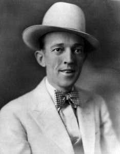 Black and white photo of Jimmie Rodgers wearing a white suit and hat.