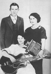 Black and white photographic image of the Carter Family. One person is holding a guitar. One looks to be holding an accordion.
