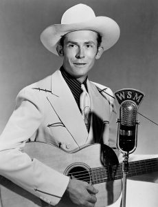 "Black and white photographic image of Hank Williams wearing a light colored suit and a hat. There is a microphone that reads ""WMS"" in front of him. He is holding a guitar."