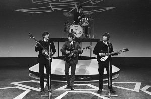 Black and white photographic image of the Beatles playing live.