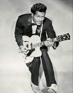 Black and white photographic image of Chuck Berry holding a white guitar.