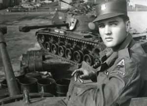 Image of Elvis near a tank.