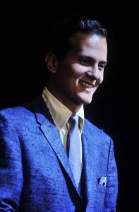 Color photographic image of Pat Boone wearing a blue jacket and blue tie with a dark background.