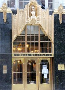 Color photographic image of the Bill Building. The building has three gold doors, glass windows, and decorative elements.