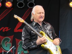 Color photographic image of Dick Dale wearing a black jacket with white lettering and holding a yellow electric guitar.
