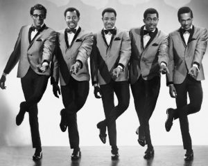 Black and white photographic image of the Temptations. There a five men in matching suits dancing together in synchronization. They have their left feet raised and the left hands pointed out towards the camera.