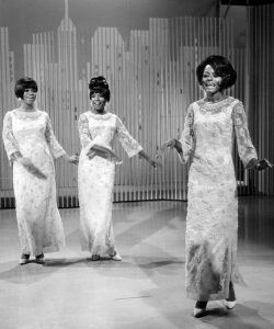 Black and white photographic image of the Supremes. There are three women in matching dresses dancing together in synchronization. The background looks like a graphic image of city scape.