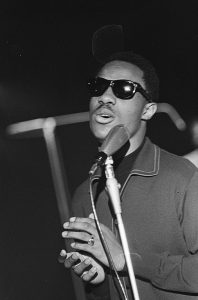Black and white photographic image of the Stevie Wonder wearing sunglasses and singing into a microphone.