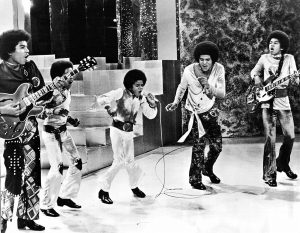 Black and white photographic image of the Jackson 5 singing in action. All of the members have afros. Two hold electric guitars. Several hold microphones.
