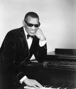Black and white photographic image of Ray Charles sitting in a suit next to a piano wearing sunglasses.