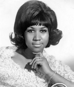Black and white photographic image of Aretha Franklin in a floral top.