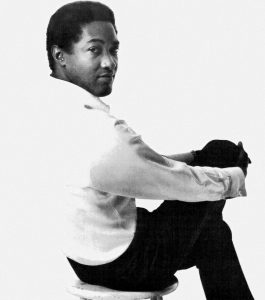 Black and white photographic image of Sam Cooke in a white shirt and black pants. He is seated away from the camera with his head turned looking back at the camera.