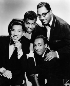 Black and white photographic image of Smokey Robinson and Miracles. There a four men in suits leaning in together looking at the camera.