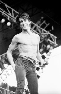 Black and white photo of Iggy Pop performing live shirtless