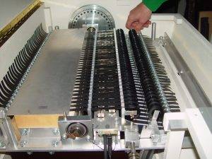 Color photo of a person changing the tape cartridge on a mellotron.