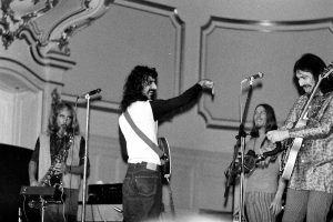 Black and white photo of Frank Zappa and band performing live