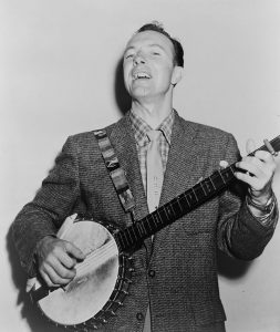 Black and white photographic image of Pete Seeger playing a banjo and singing.