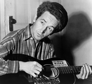 "Black and white photographic image of Woody Guthrie playing a guitar. The sticker on the guitar appears to read ""Kills fascists"""