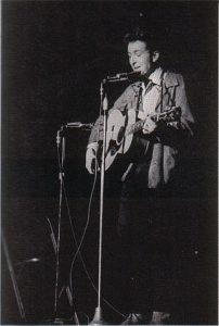 Black and white photographic image of Bob Dylan playing a guitar and singing into a microphone. It appears that he might be performing.