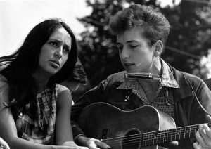 Black and white photographic image of Bob Dylan playing a guitar and singing into a harmonica with Joan Baez.
