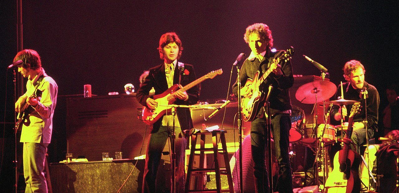 Color image of Bob Dylan and The Band. There are three guitarists and one drummer pictured. The picture has a red-yellow glow to it.