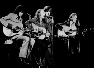 Black and white photographic image of Crosby, Stills, and Nash performing. There are four men in this photo. Three of the four have guitars.