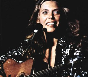 Color photographic image of Joni Mitchell playing a guitar with a microphone.