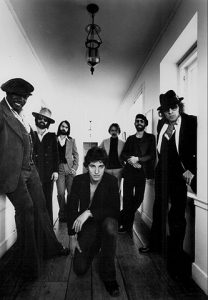 Black and white photo of Bruce Springsteen (center) and the E Street Band (behind him).