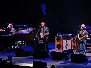 Color photo of Phish live with blue lights in the background.