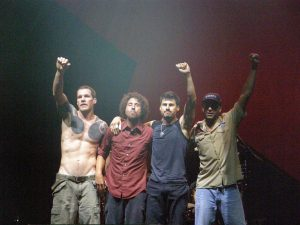 Color photo of Rage Against the Machine. Three of the four members are raising their fists.