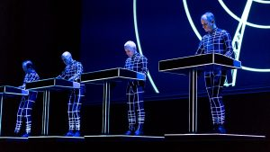 Color photo of Kraftwerk live dressed up with blue-purple lighting highlighting the white lines on their outfits.