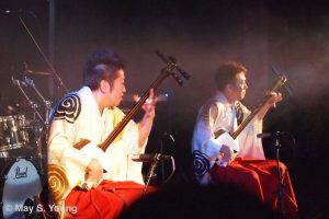 Yoshida brothers sitting and playing guitars.