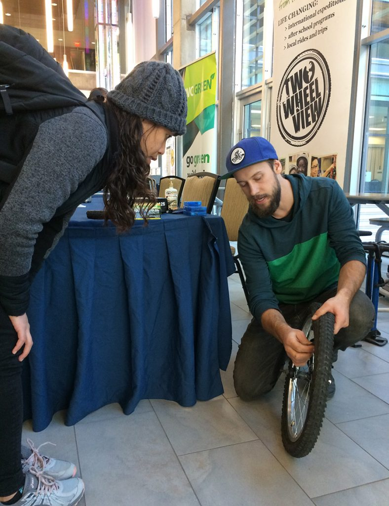 """<img src=""""DIY_Green_Fair_Two_Wheel_Christine_2.jpg"""" alt=""""student demonstrating to another how to repair bicycle tire"""">"""