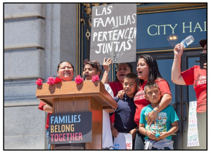 """Photograph: Protesters with Causa Justa / Just Cause speak on the steps of San Francisco City Hall for a """"Families Belong Together"""" rally. One holds a sign reading """"Las Familias Pertenecen Juntas"""""""