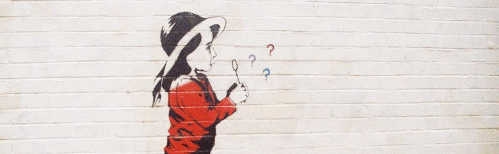 Wall art of a little girl blowing bubbles shaped like question marks