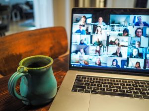 A coffee cup sits next to a laptop open to a virtual meeting with multiple individuals