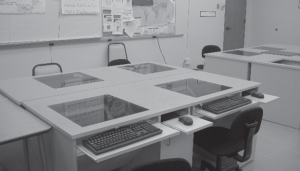 A desk designed to seat four people with recessed monitors, enabling all four students to have individual computer access without monitors obstructing their ability to see and talk to one another.