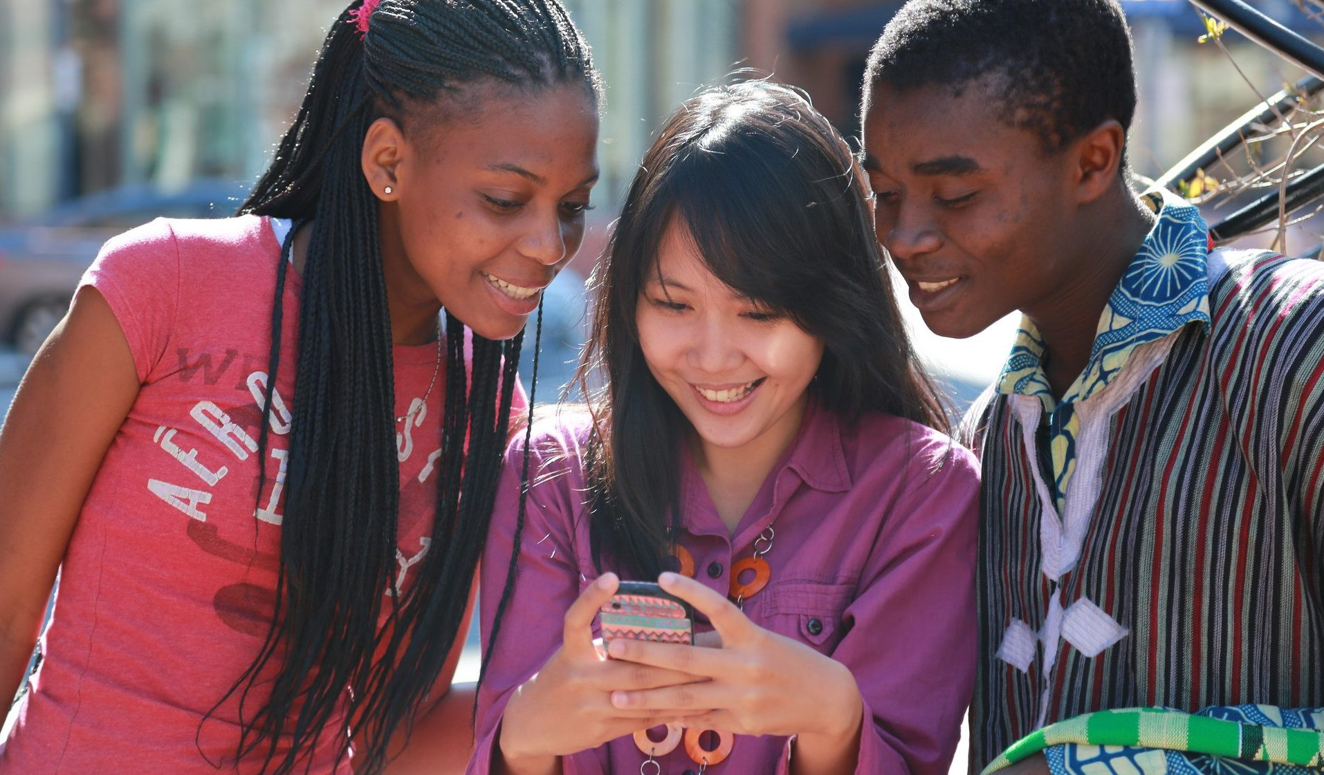 Three teenagers looking at a smartphone and smiling