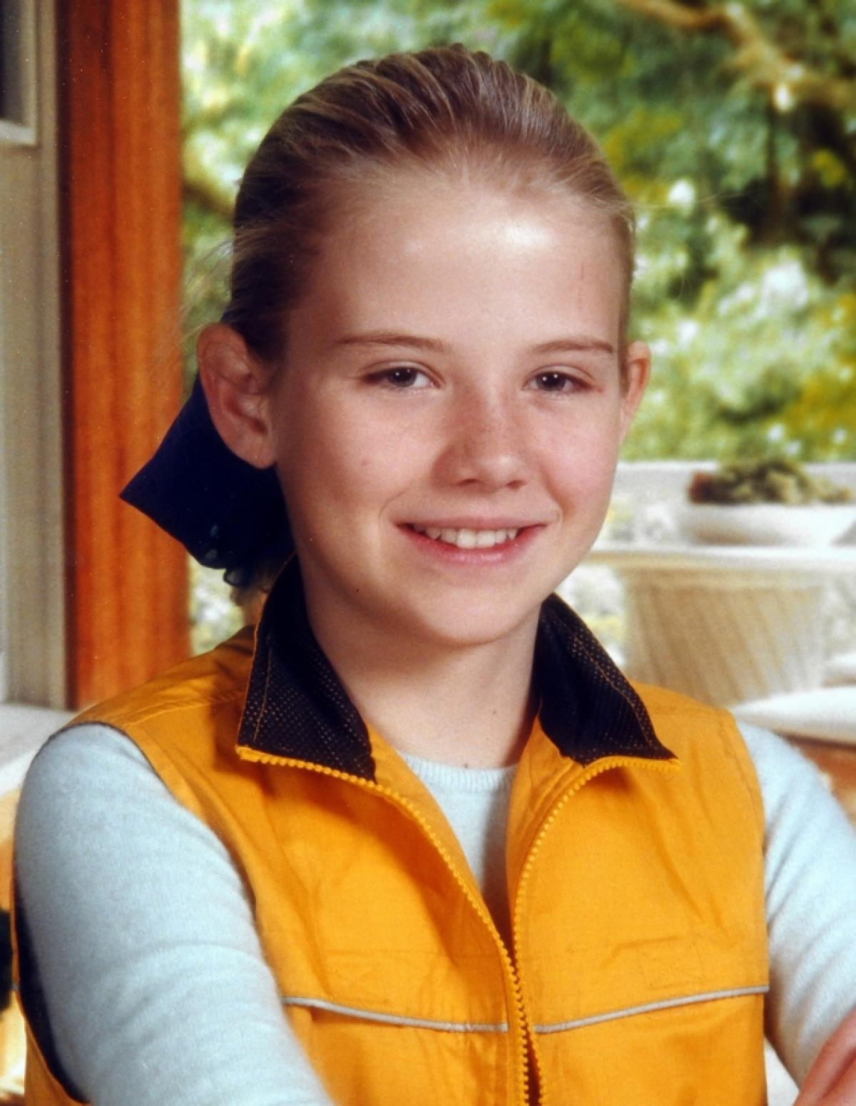A photo of Elizabeth Smart as a little girl. She sits smiling at the camera in a yellow vest and long-sleeved white shirt.