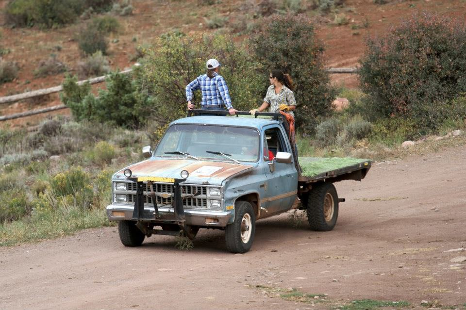 Photograph showing two people riding in the back of a flat-bed truck on a dirt road, holding onto a bar across the top of the truck