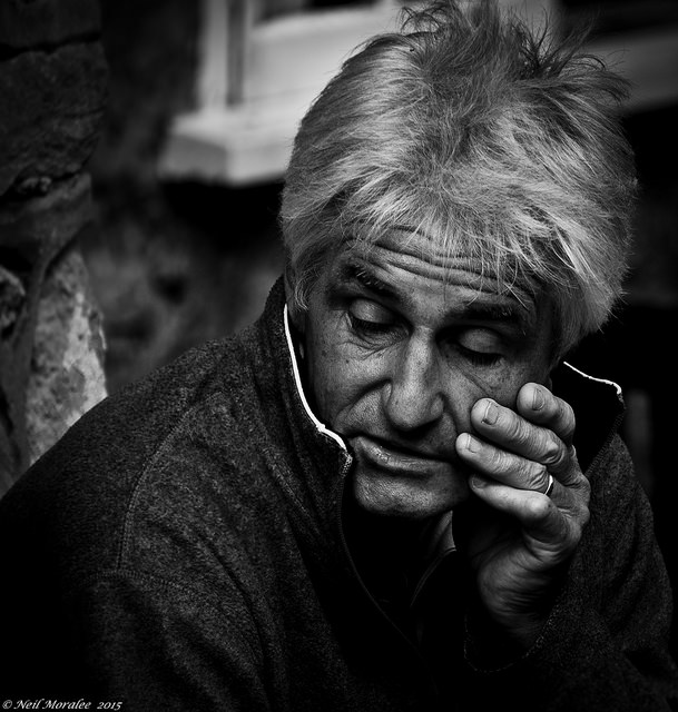 An old man sitting on the street
